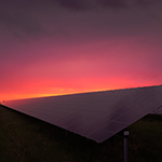 Picture of solar panels and red sunrise
