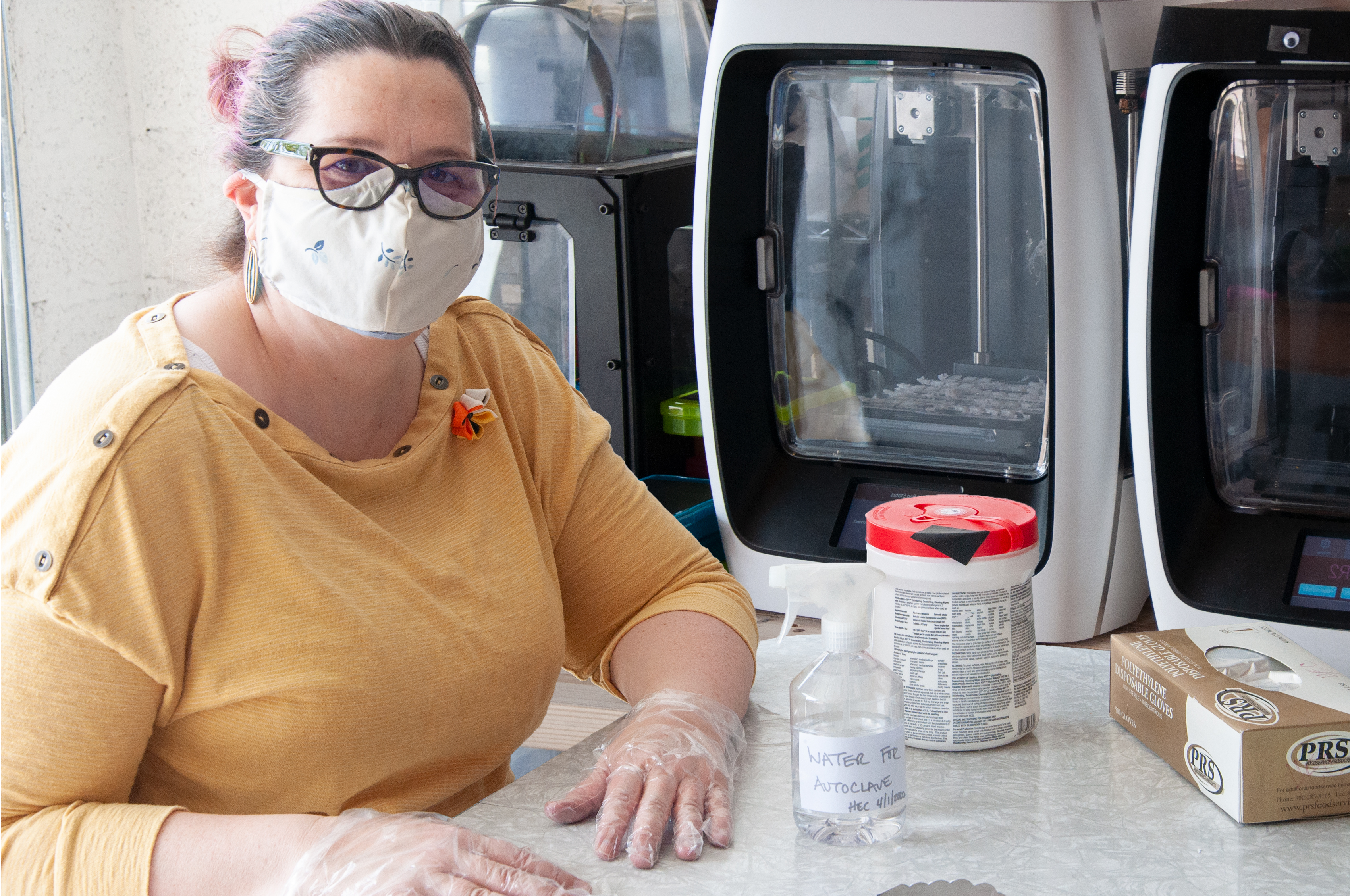 Professor Heather Canavan in her garage lab with 3D printers making protective face masks.
